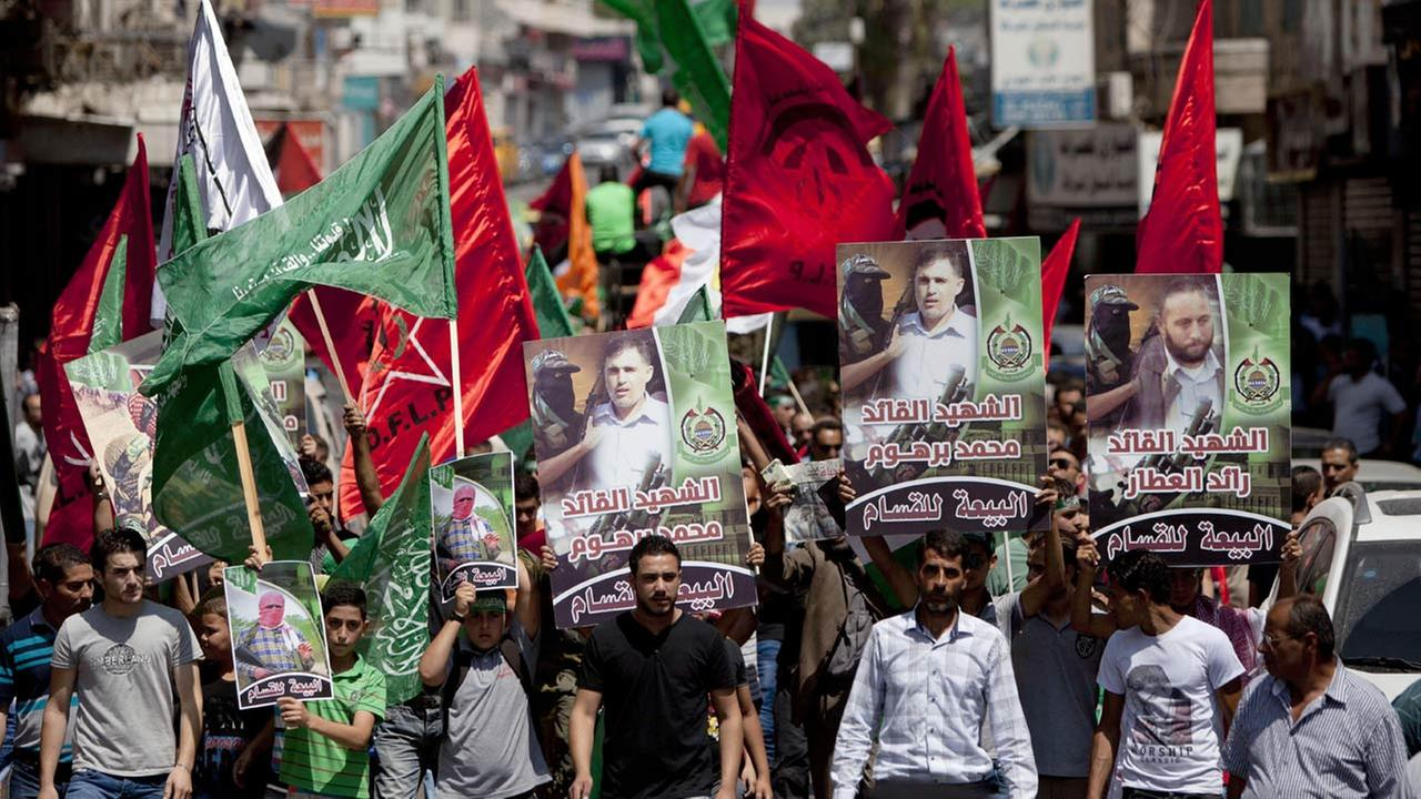 Supporters of Hamas hold posters of three senior commanders of the Hamas military wing, Mohammed Abu Shamaleh, Raed Attar and Mohammed Barhoum, who were killed Thursday.