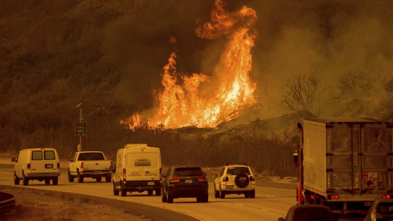Flames from a wildfire leap above traffic on Highway 101 north of Ventura, Calif., on Wednesday, Dec. 6, 2017.