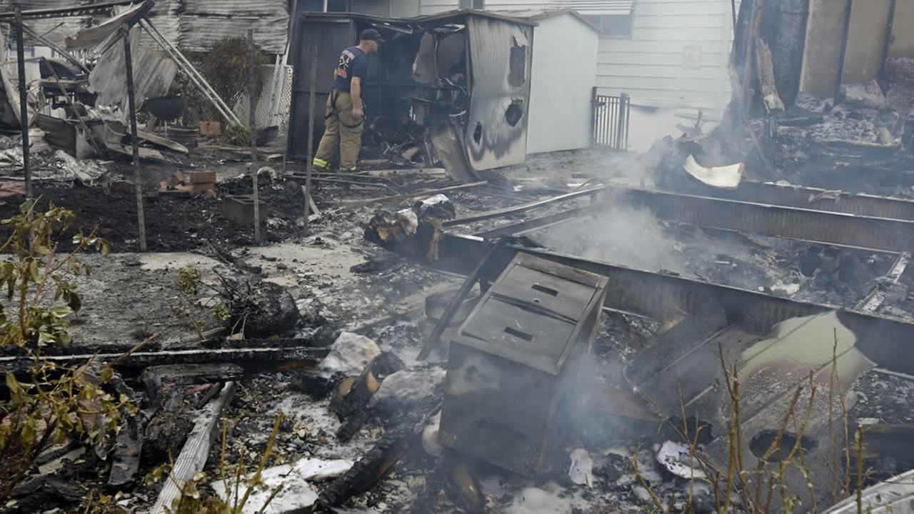 A Napa firefighter inspects one of four mobile homes that were destroyed in a gas fire Sunday, Aug. 24, 2014, at the Napa Valley Mobile Home Park, in Napa, Calif. Ben Margot