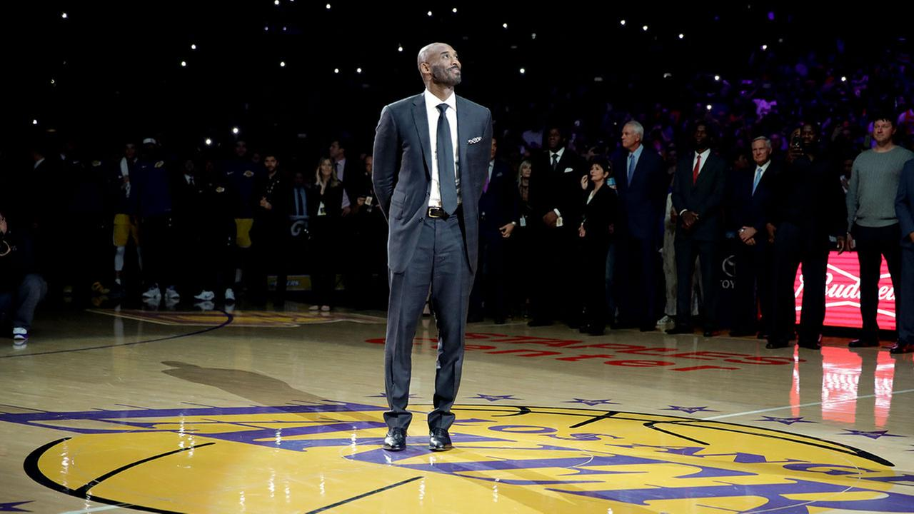 Former Los Angeles Laker Kobe Bryant arrives for a halftime ceremony, retiring both of his jerseys during an NBA basketball game in Los Angeles, Monday, Dec. 18, 2017.
