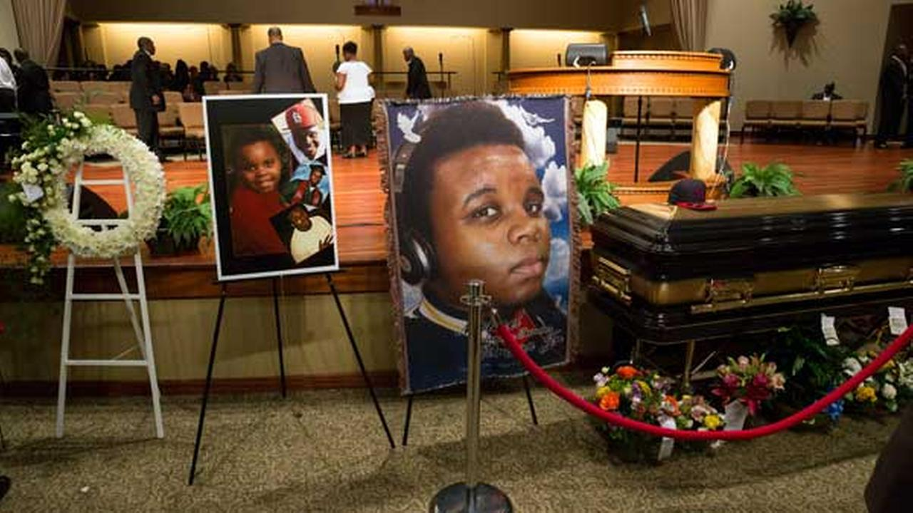 Photos surround the casket of Michael Brown before the start of his funeral at Friendly Temple Missionary Baptist Church in St. Louis, Monday, Aug. 25, 2014.