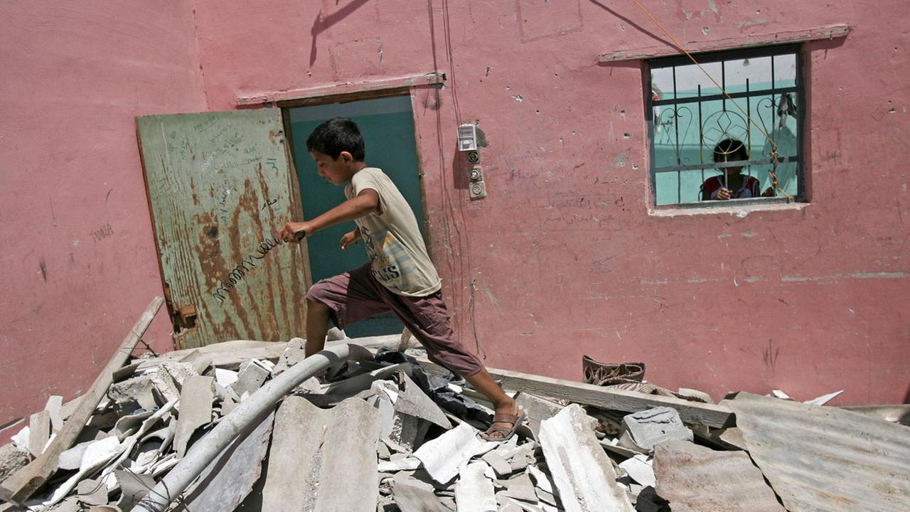 A Palestinian boy walks on the rubble of a house after it was hit by an Israeli airstrike in the Rafah refugee camp in the southern Gaza Strip early Tuesday, Aug. 26, 2014.