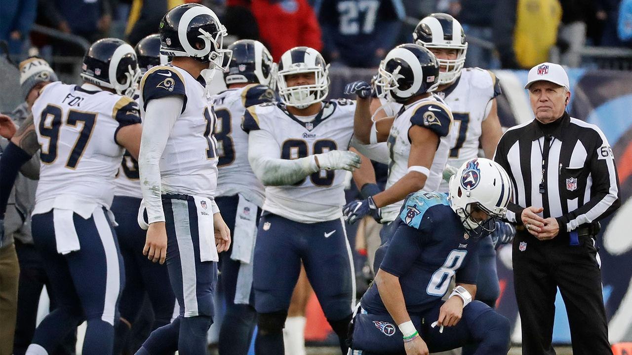 Tennessee Titans quarterback Marcus Mariota gets up as Los Angeles Rams players celebrate after the Titans final drive ended and the Rams took possession in the final minutes.