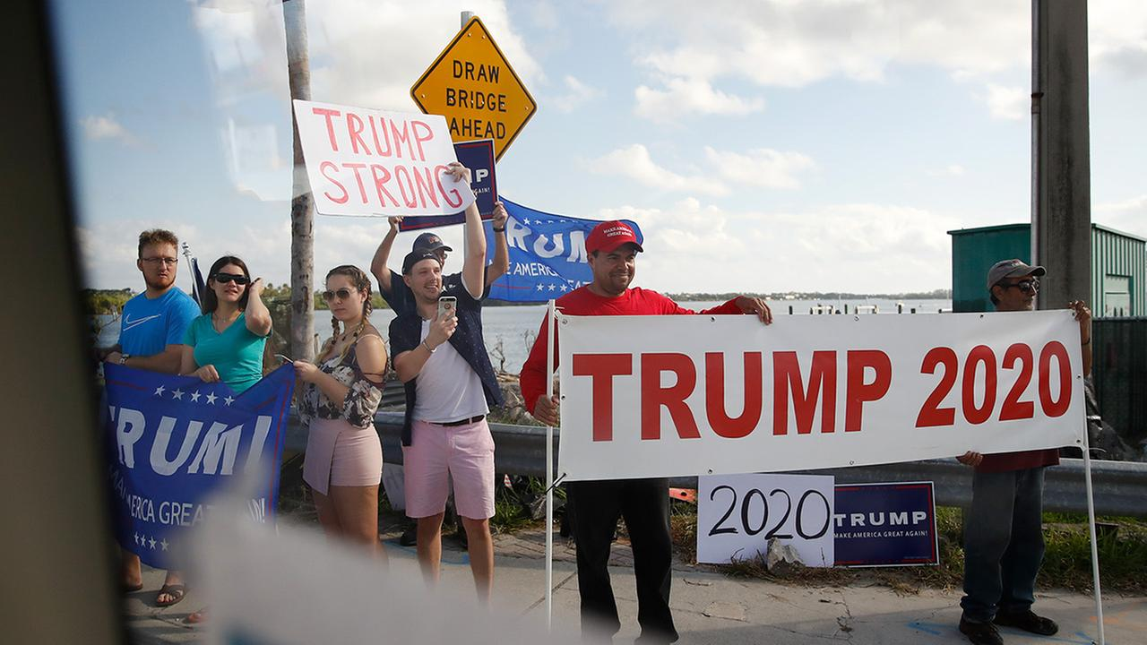 A group of President Trump supporters is seen from a van traveling in the presidents motorcade en route to his Mar-a-Lago estate in Palm Beach, Fla., Tuesday, Dec. 26, 2017.
