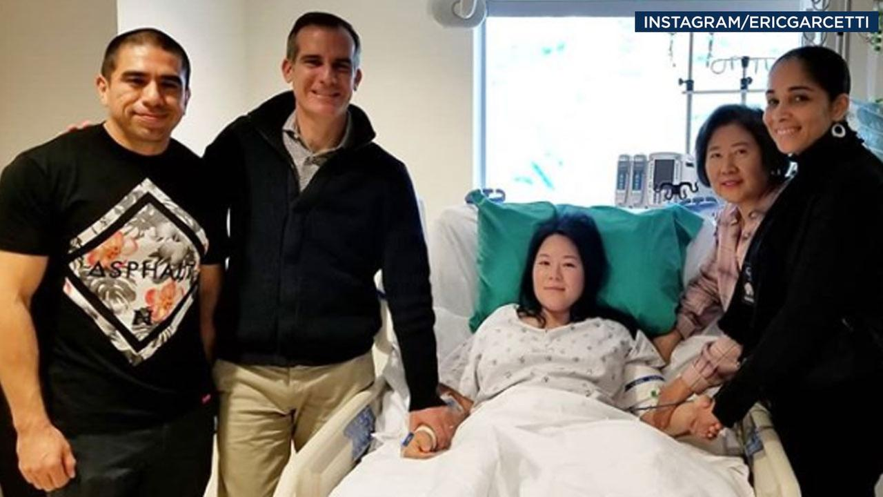 LAPD Officer Joy Park smiles while in a hospital bed as she takes a photo with Mayor Eric Garcetti and family members.