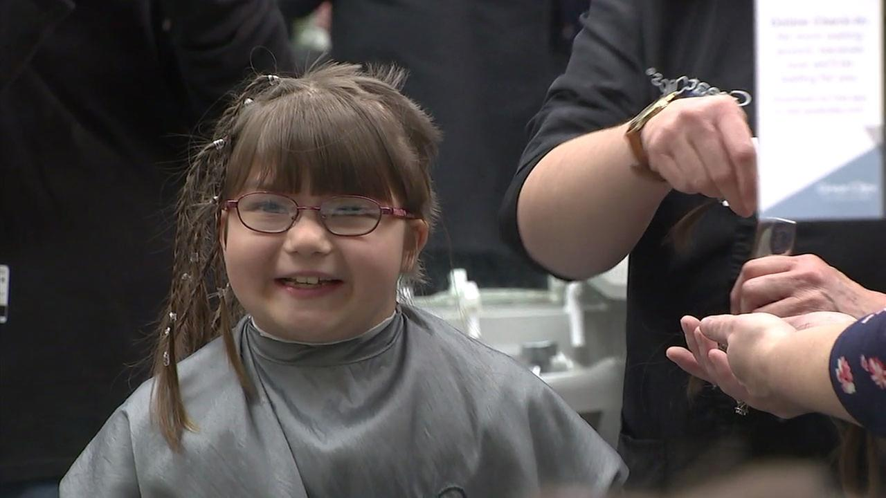 Thalia Noble, 9, is shown smiling in a chair at a Santa Ana salon as she donates 14 inches of her hair to help other children with medical conditions.