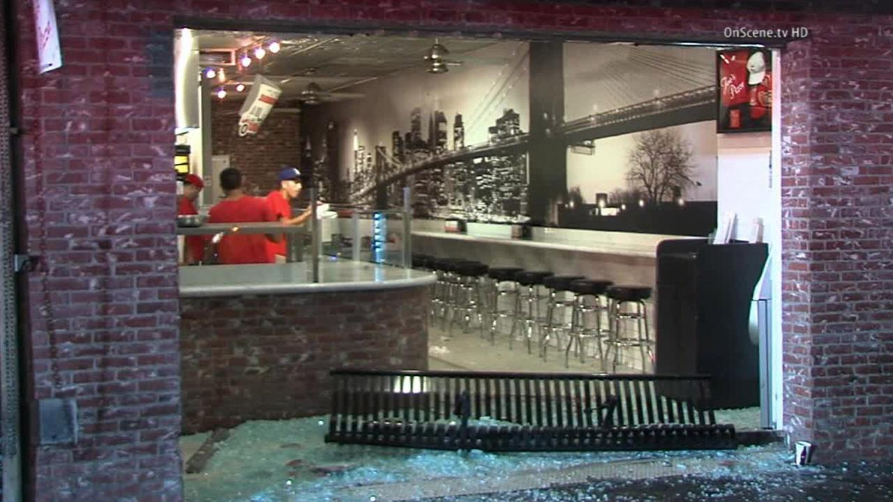 Employees clean up Joes Pizza, which had its front window shattered after a hit-and-run driver sent a bench flying on Saturday, Aug. 30, 2014.