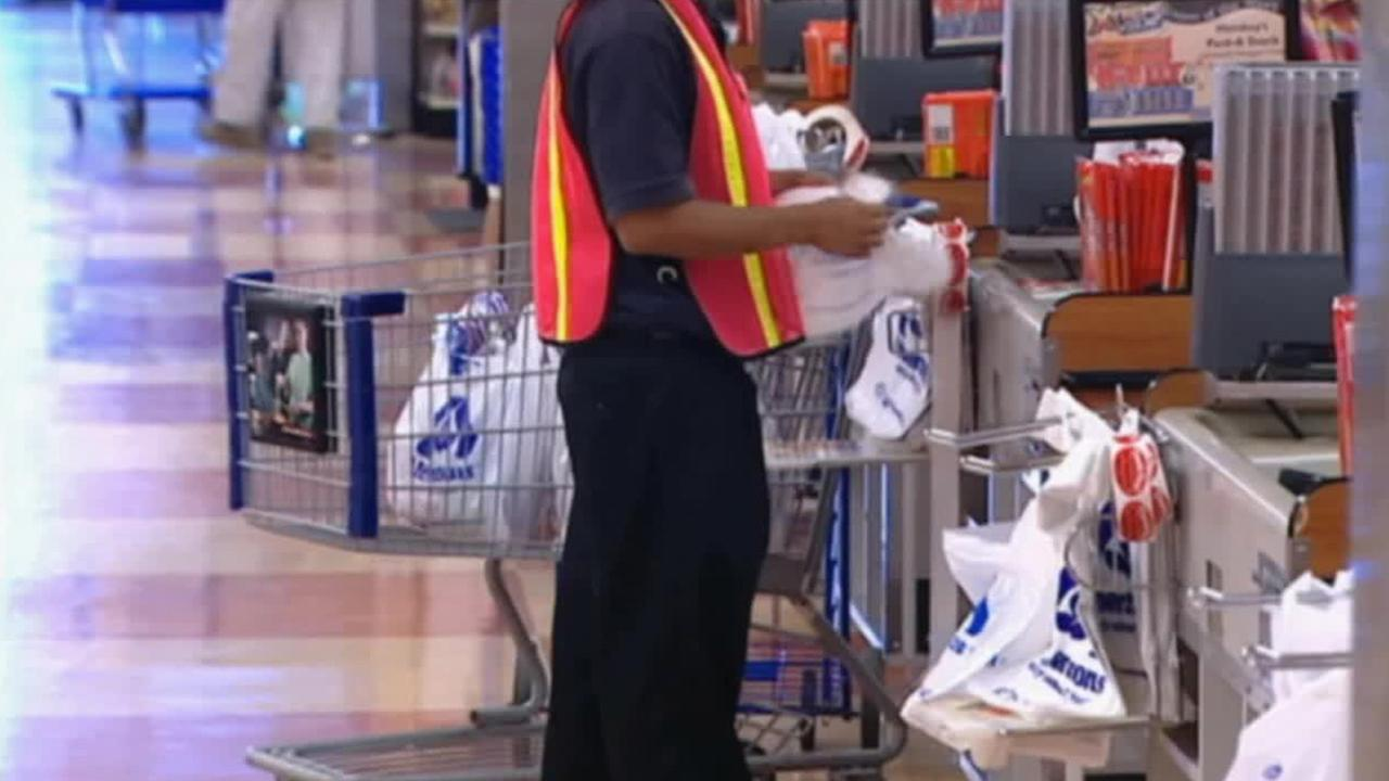 An Albertsons employee helps bag groceries with plastic bags in this undated file photo.