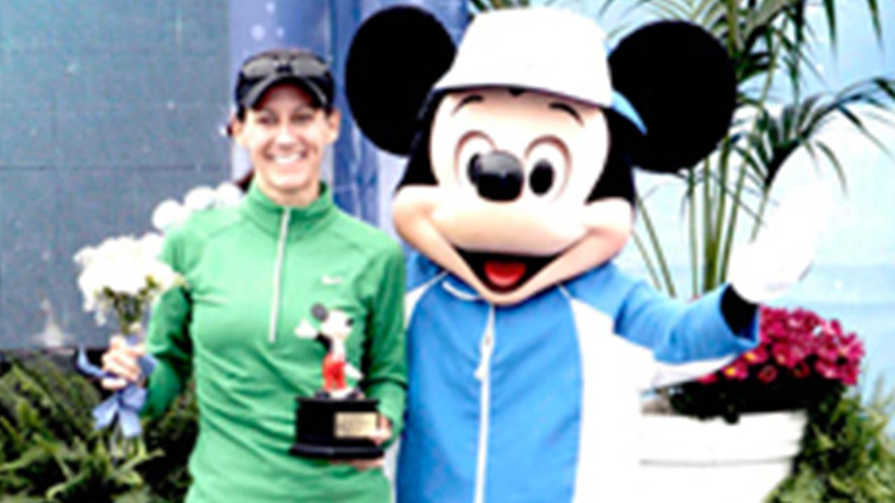 A runner takes a picture with Mickey Mouse after completing the Disneyland Half Marthon in this undated file photo.