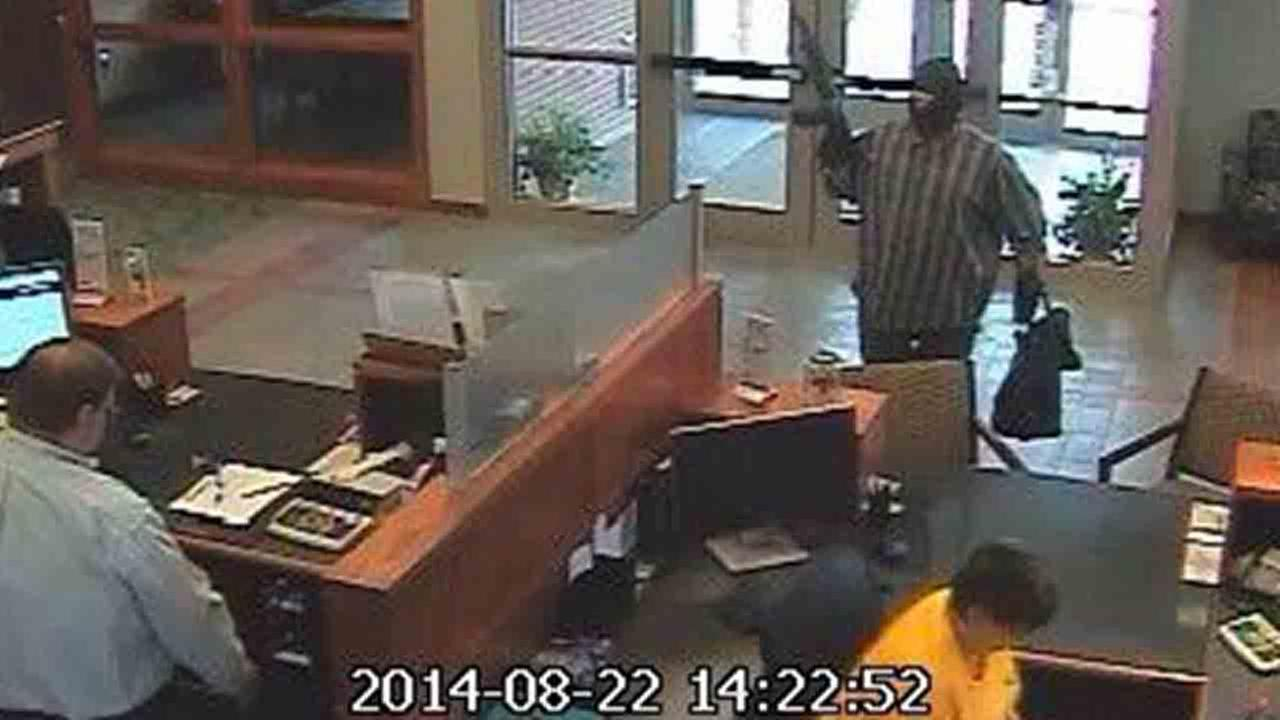 A bank robbery suspect dubbed the AK-47 Bandit is seen in this August 2014 surveillance video from a Nebraska bank.