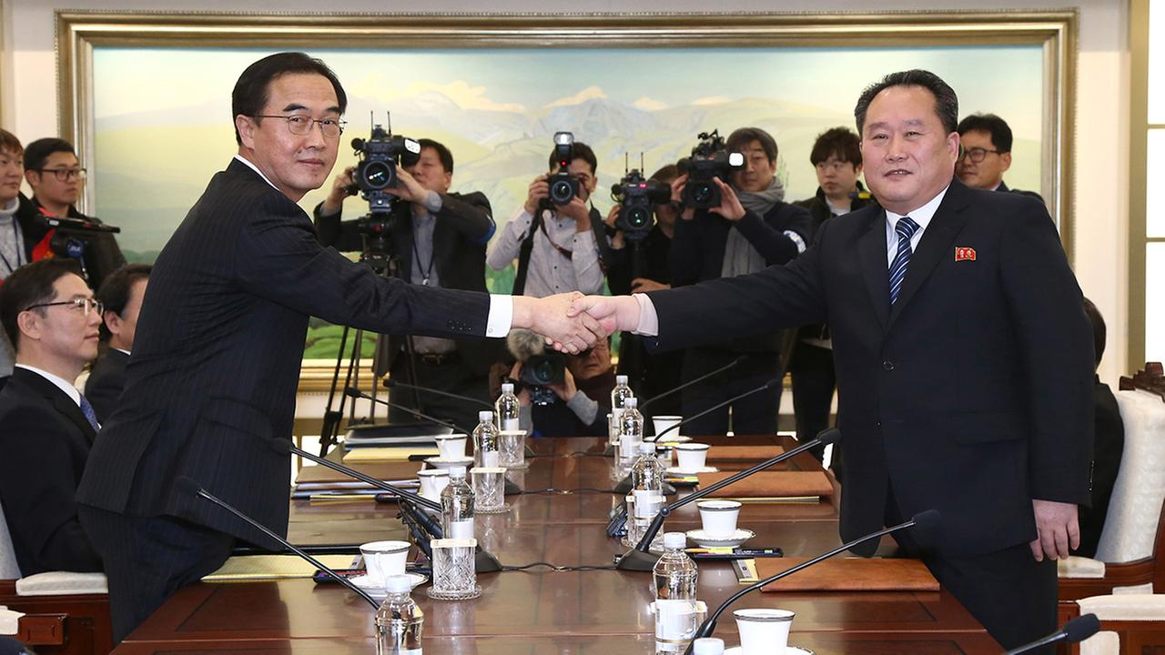 South Korean Unification Minister Cho Myoung-gyon, left, poses with head of North Korean delegation Ri Son Gwon while shaking hands during their meeting at the Panmunjom.