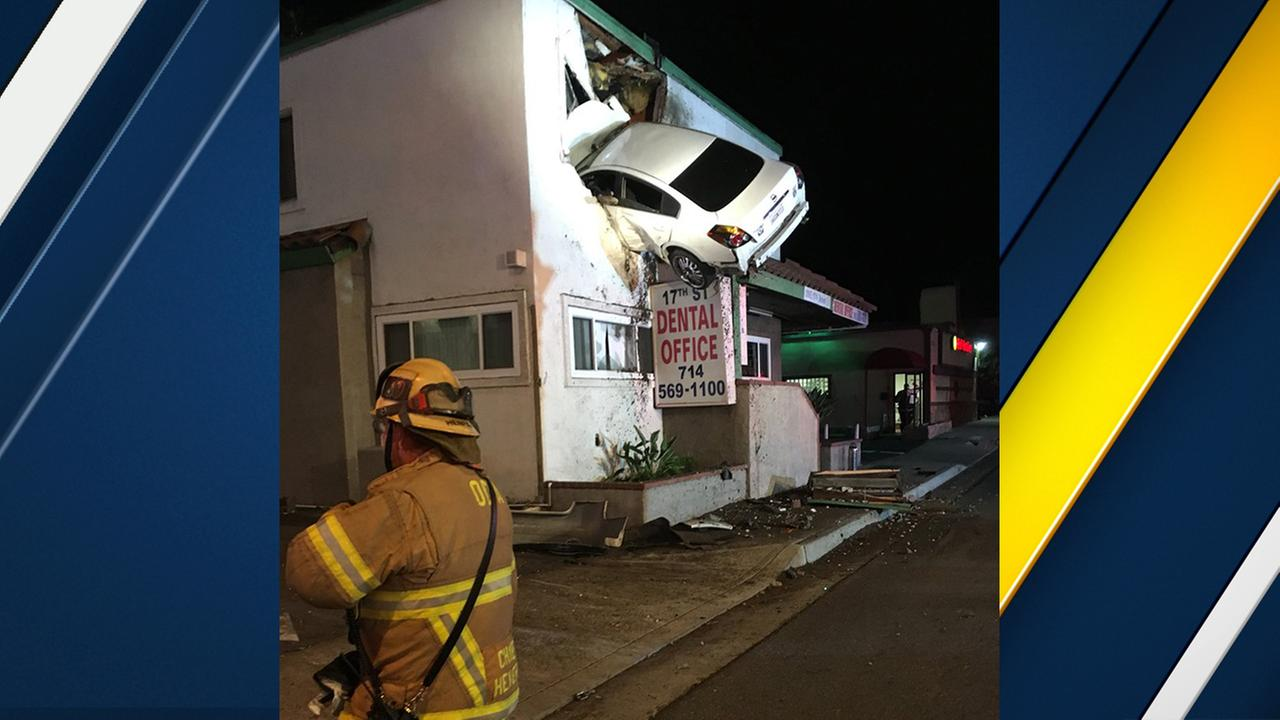 Auto soars into second floor of building, gets lodged for hours