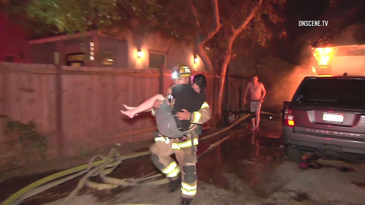 An Orange County firefighter carried a woman to safety as a Santa Ana home was consumed by flames on Sunday, Jan. 14, 2018.