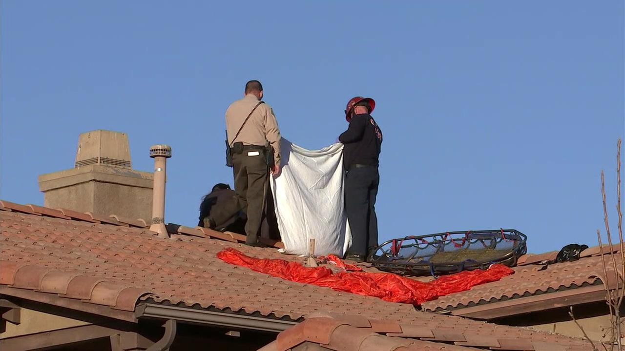 A Riverside County sheriffs deputy and firefighter stand over a deceased skydiver on the roof of a Perris home on Monday, Jan. 22, 2018.