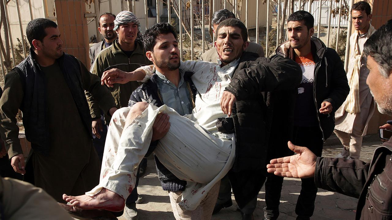 A wounded man is assisted at the site of a deadly suicide attack in the center of Kabul, Afghanistan, Saturday, Jan. 27, 2018.