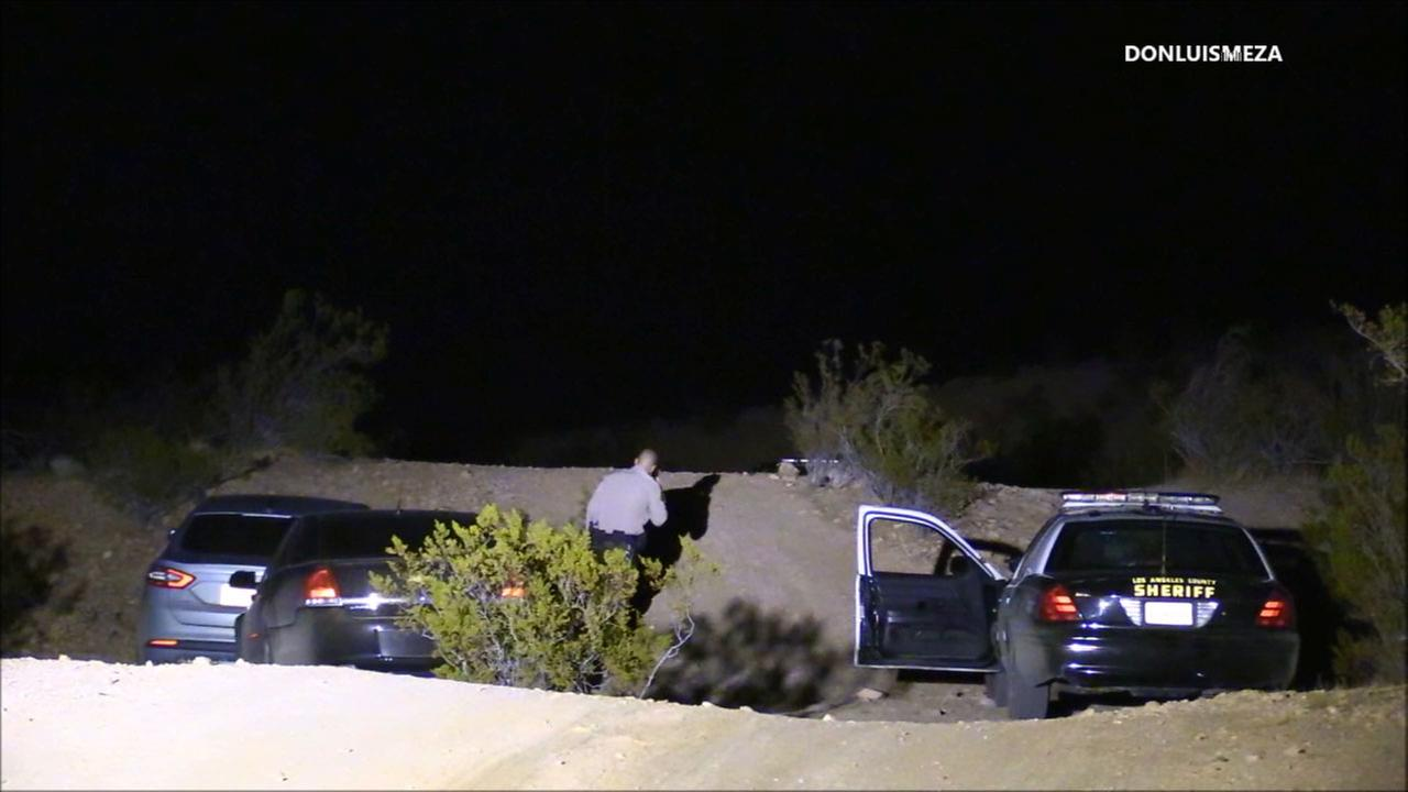 LASD deputies investigate a scene in Lancaster where a body and a truck matching the description of a homicide suspect were found on Sunday, Feb. 4, 2018.