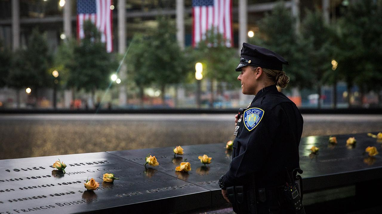 A Port Authority officer takes a moment to herself before family members are let in for the memorial observances held at the site of the World Trade Center on Sept. 11, 2014.