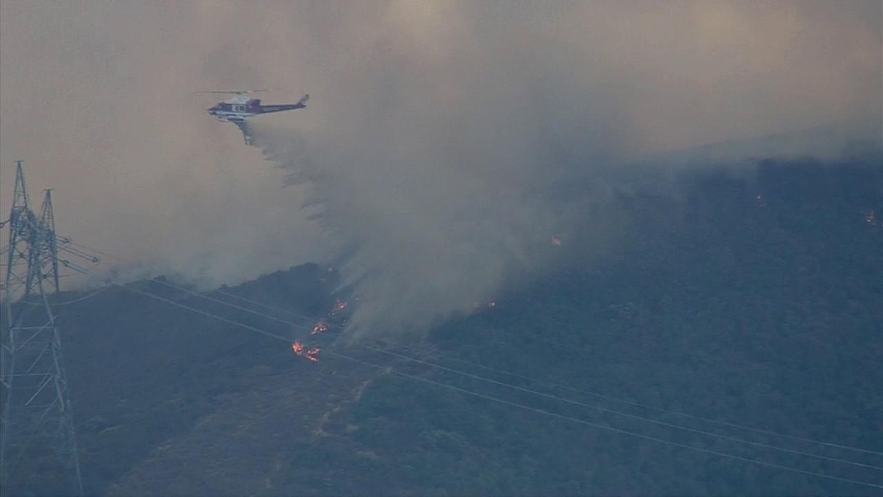 A helicopter makes a water drop on flames in Silverado Canyon Friday, Sept. 12, 2014.