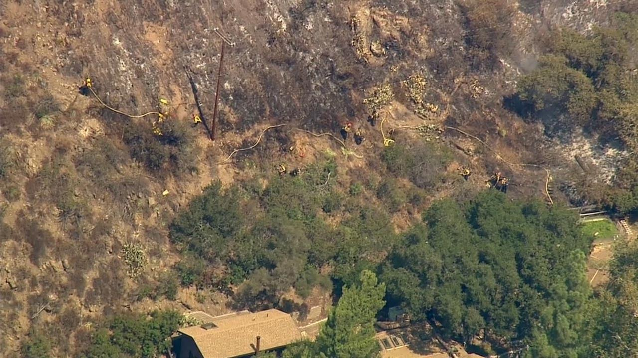Firefighters provide structure protection after a brush fire erupted in Silverado Canyon Friday, Sept. 12, 2014.