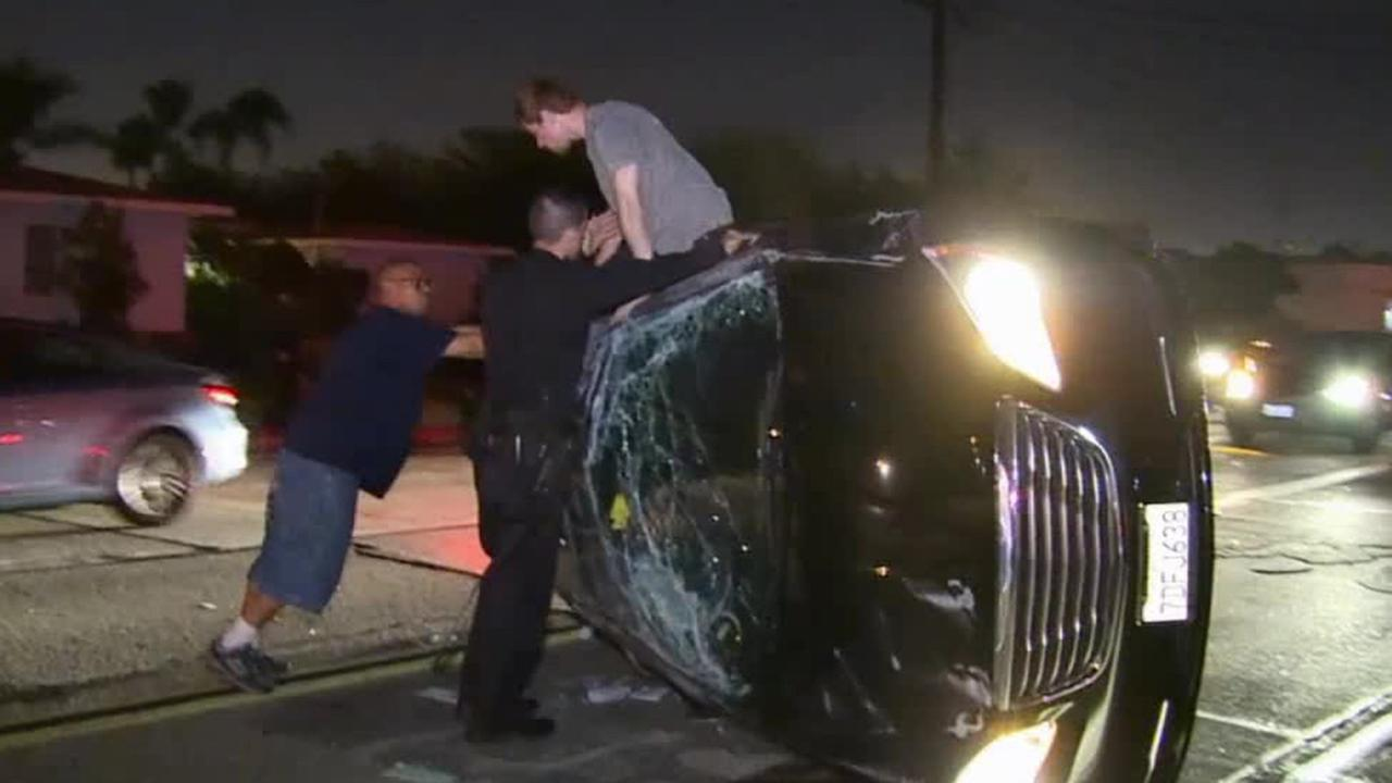 Authorities help a man exit an overturned car involved in an alleged DUI crash on Friday, Sept. 12, 2014.
