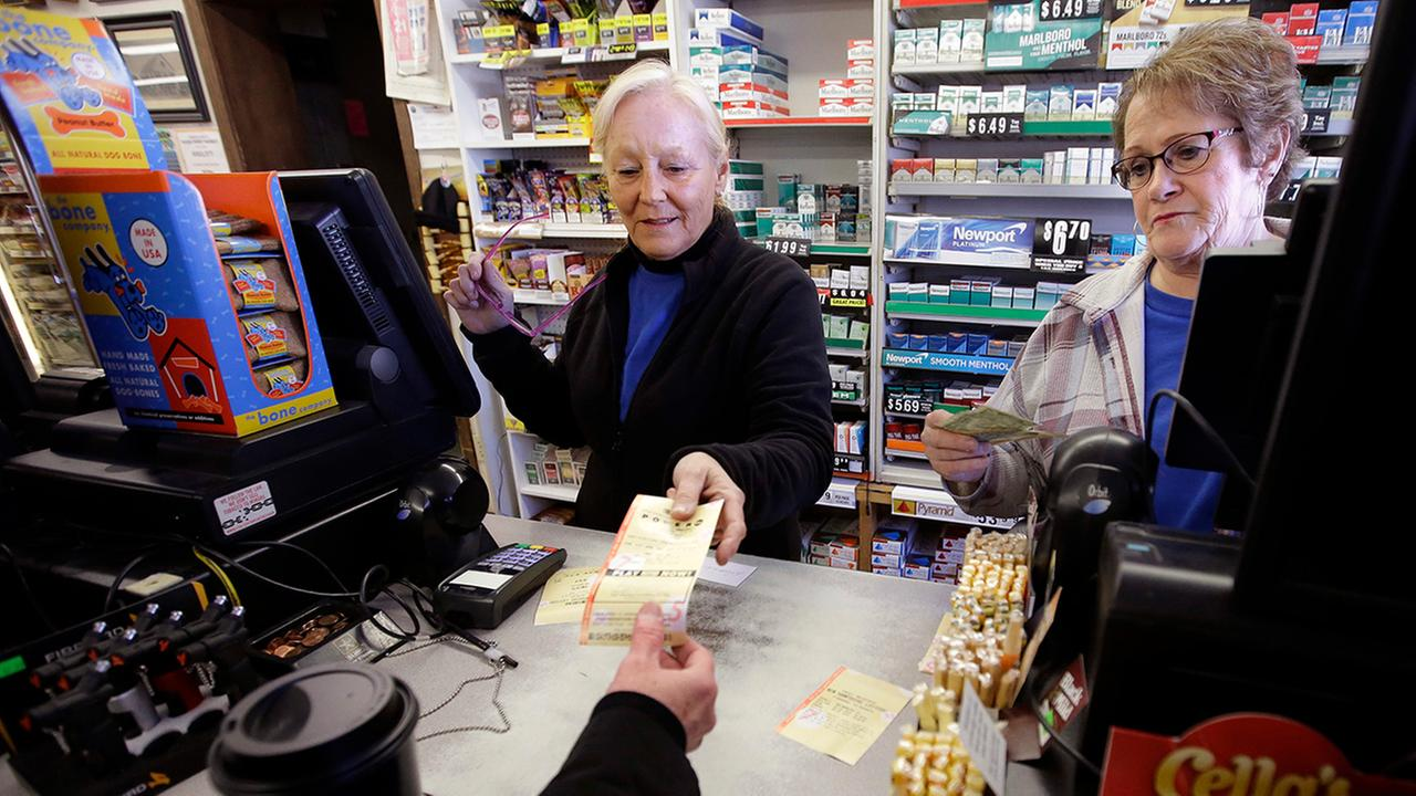 Cashiers Kathy Robinson, left, and Ethel Kroska, right, both of Merrimack, N.H., sell a lottery ticket at Reeds Ferry Market convenience store in Merrimack.