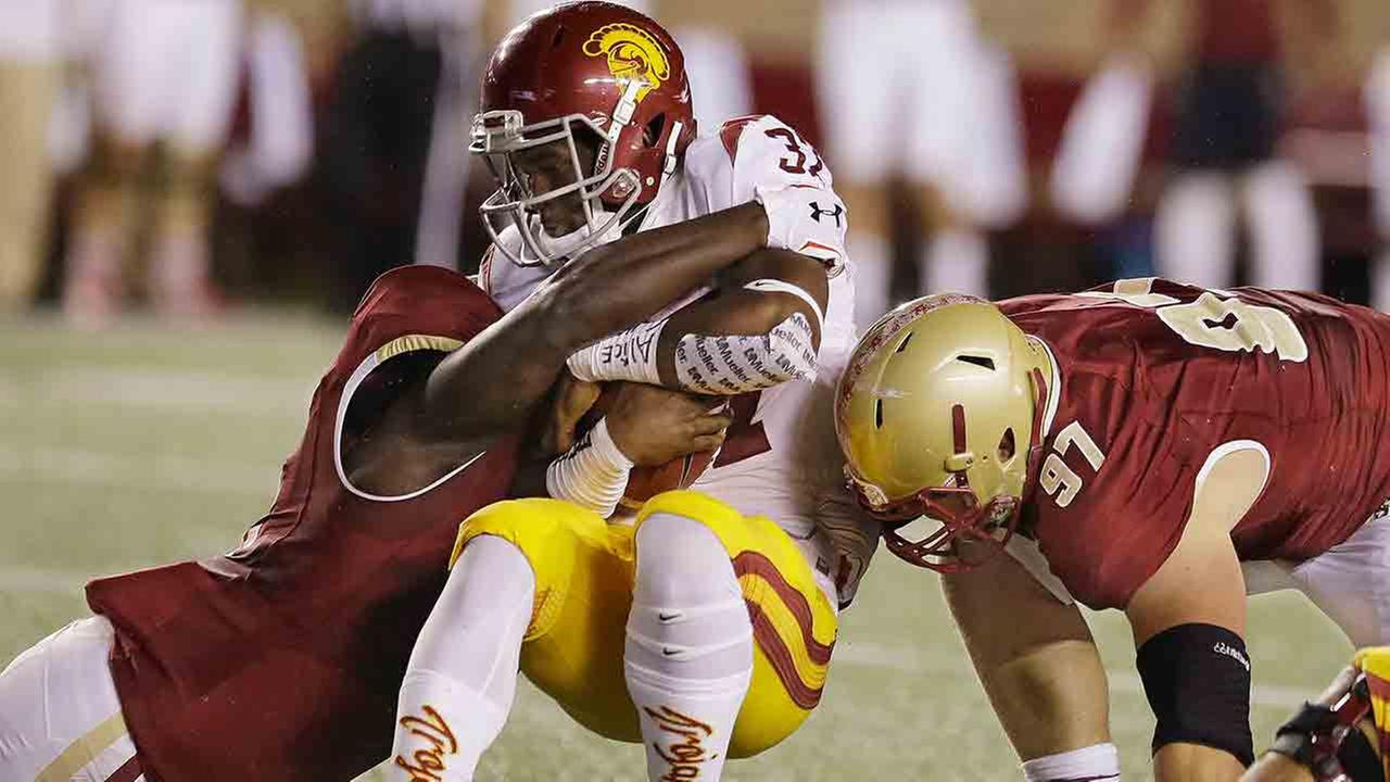 USC running back Javorius Allen (37) is tackled by Boston College defensive tackle Truman Gutapfel (97) and linebacker Steven Daniels, left, Saturday, Sept. 13, 2014 in Boston.