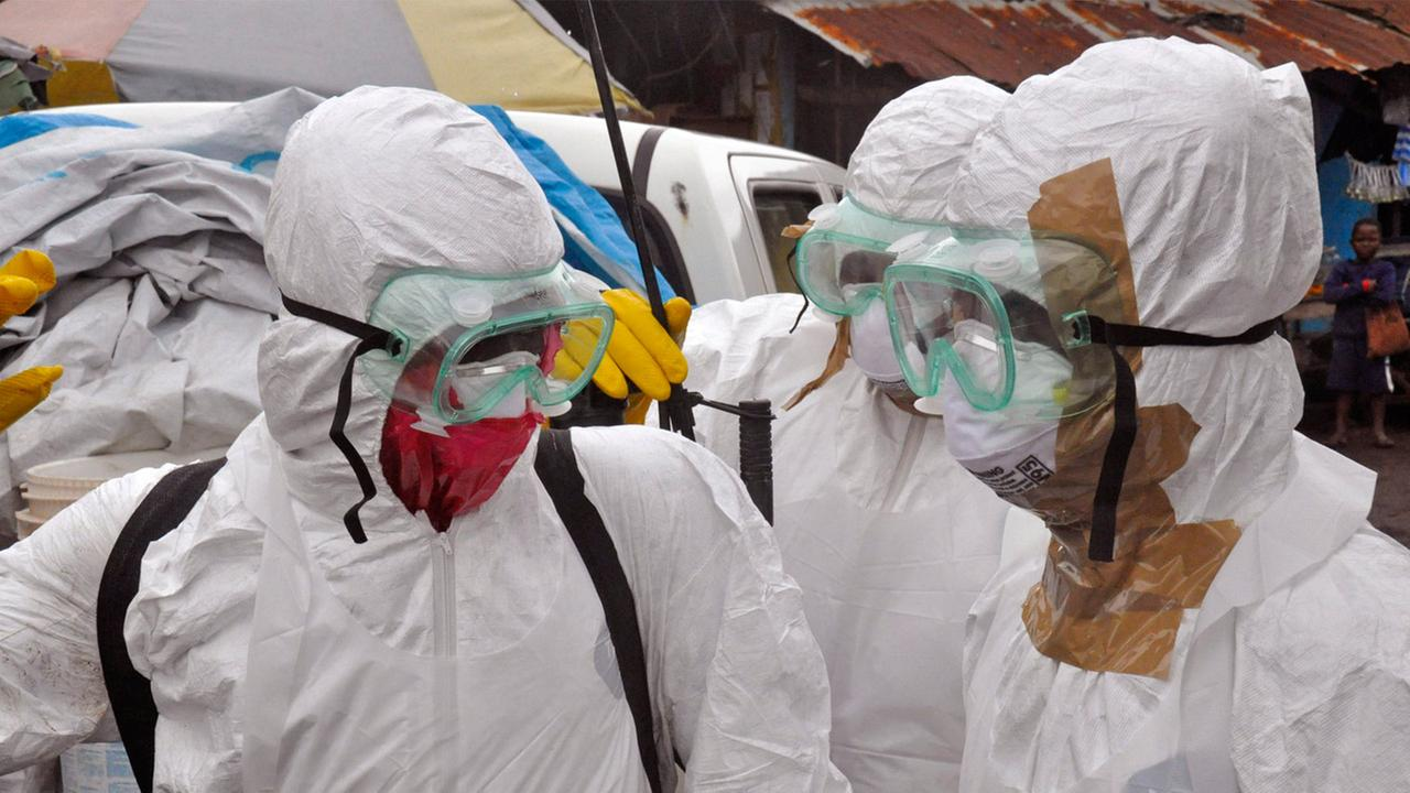 Health workers in protective gear leave after carrying the body of a woman they suspect died from the Ebola virus, in an area known as Clara Town in Monrovia, Liberia, Sept. 10.