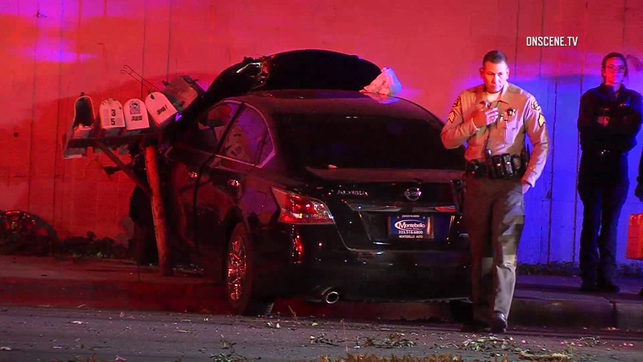 A Los Angeles County sheriffs deputy is seen near a wrecked sedan after a triple shooting near Whittier on Saturday, Feb. 24, 2018.