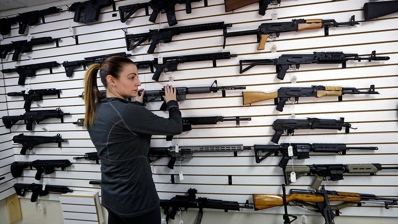 Gun shop owner Tiffany Teasdale-Causer returns a Ruger AR-15 to its place on a wall with dozens of other semi-automatic rifles, Tuesday, Nov. 7, 2017, in Lynnwood, Wash.