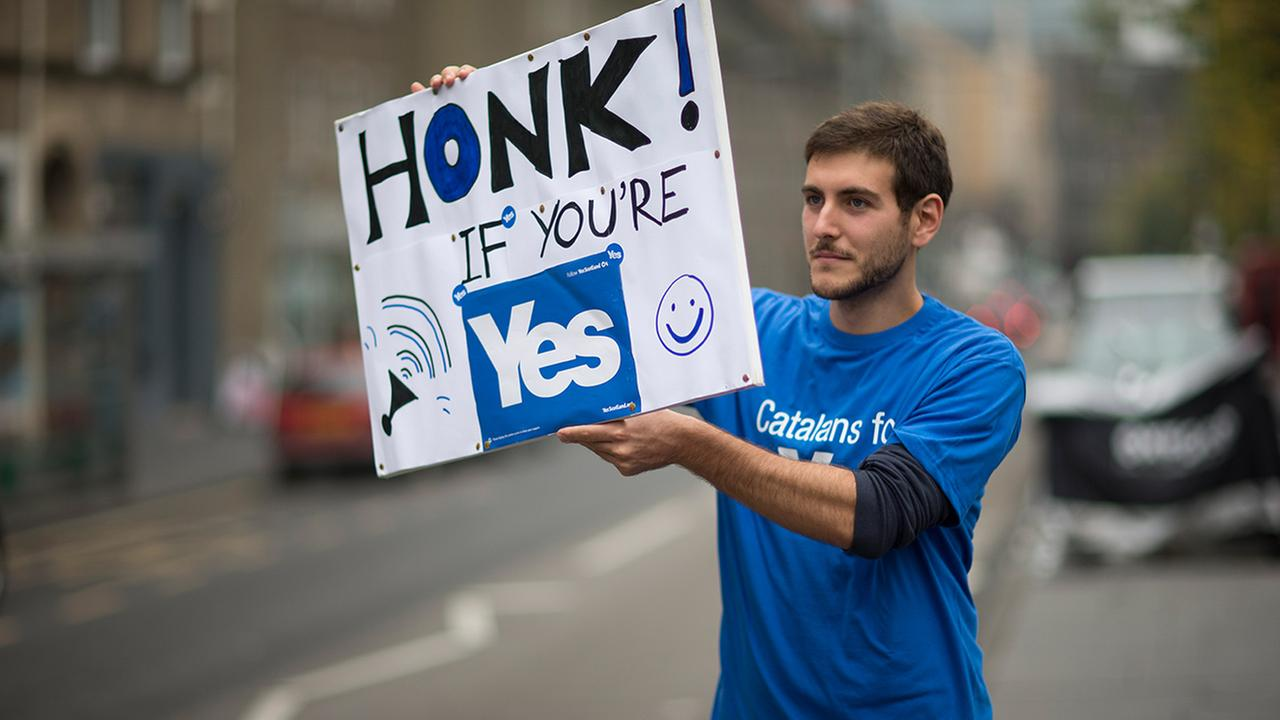 David Aguilar from Catalonia, who is visiting Scotland to support the Scottish independence referendum, holds up a placard supporting a Yes vote at passing motorists in Edinburgh.