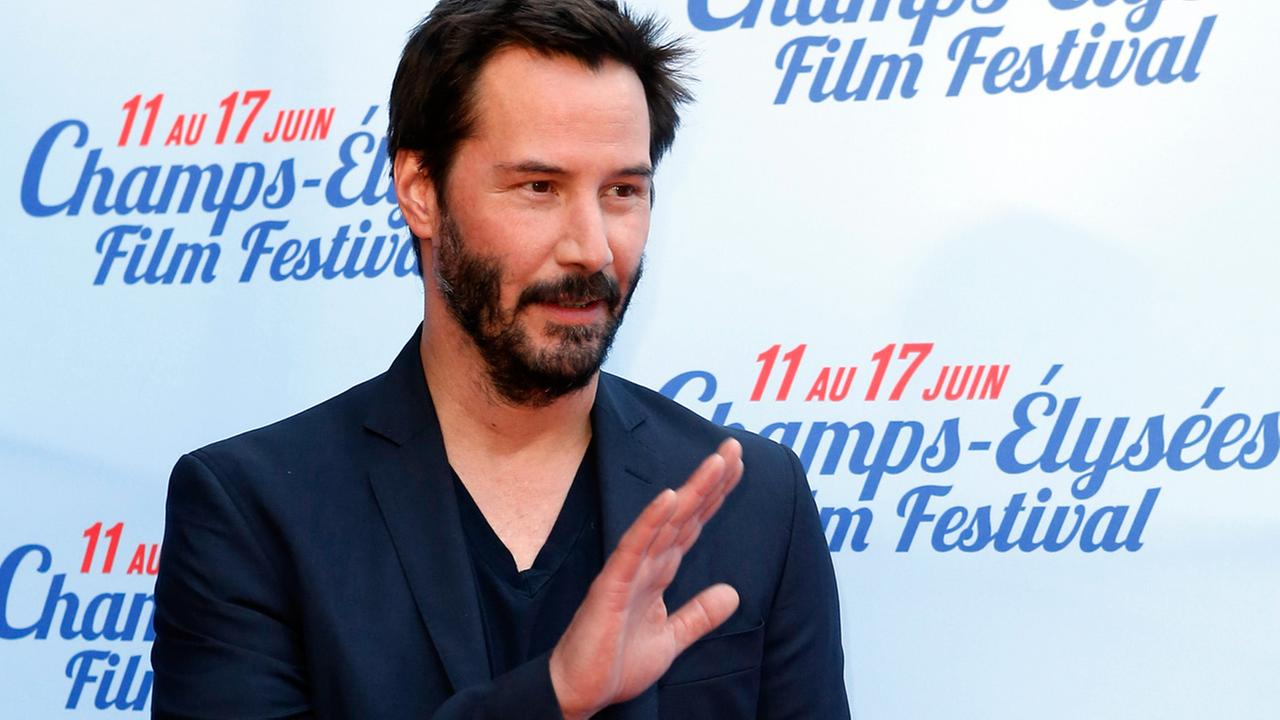Keanu Reeves waves at the screening of the film Side by Side during the Champs-Elysees Film Festival, in Paris, Saturday, June 14, 2014.