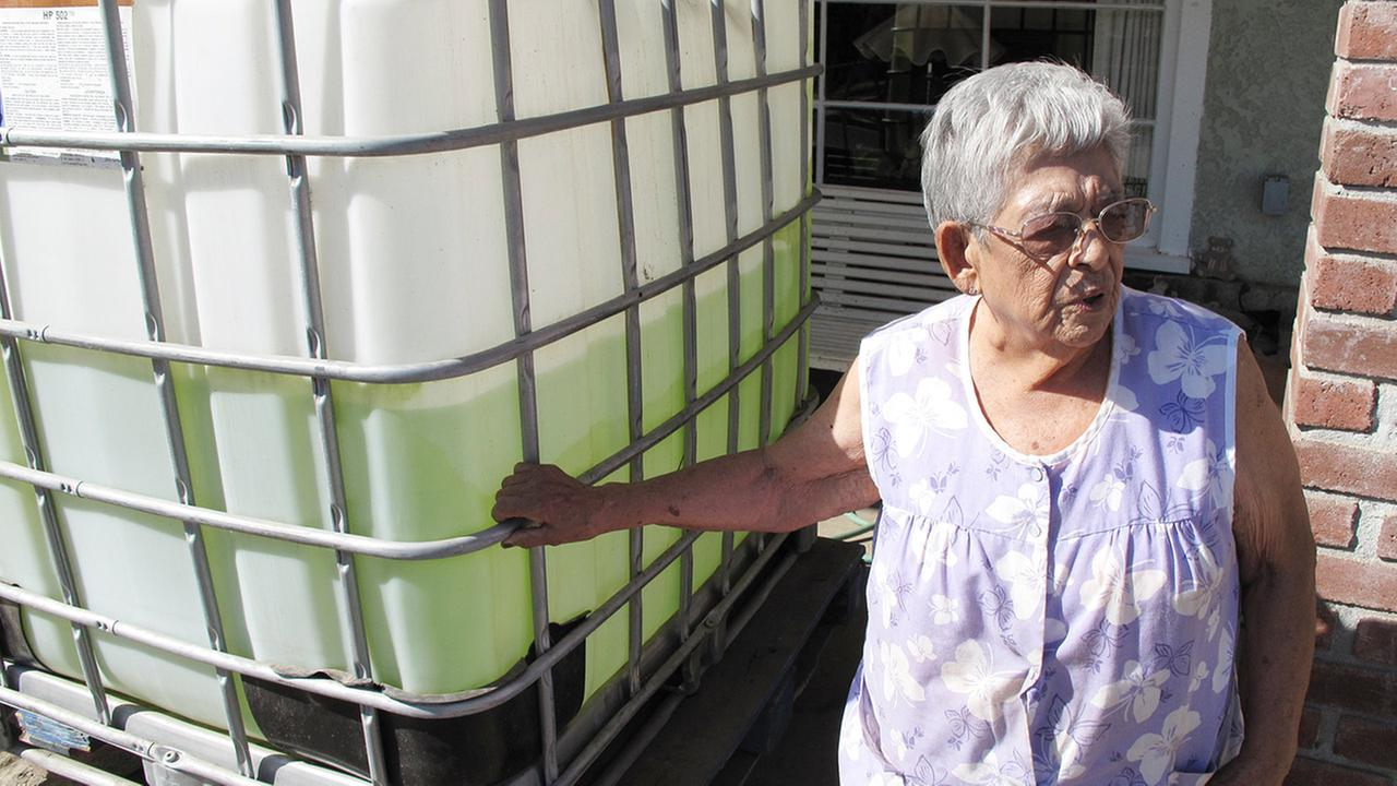 Vickie Yorba, 94, stands next to a water tank in front of her home in East Porterville, Calif., where she has lived for 66 years.