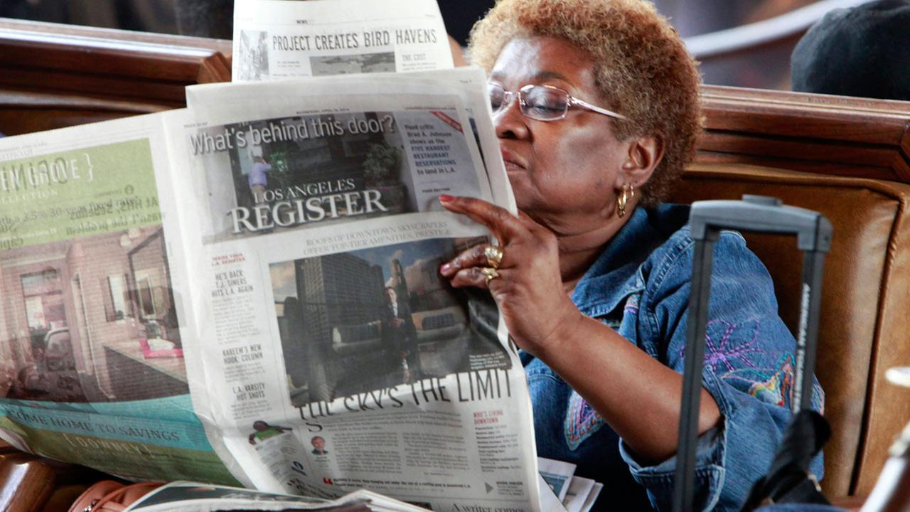 In this April 16, 2014 file photo, Dorothy Shumrt reads the Los Angeles Register newspaper on the day of its launch while waiting for a train at Union Station, in Los Angeles.