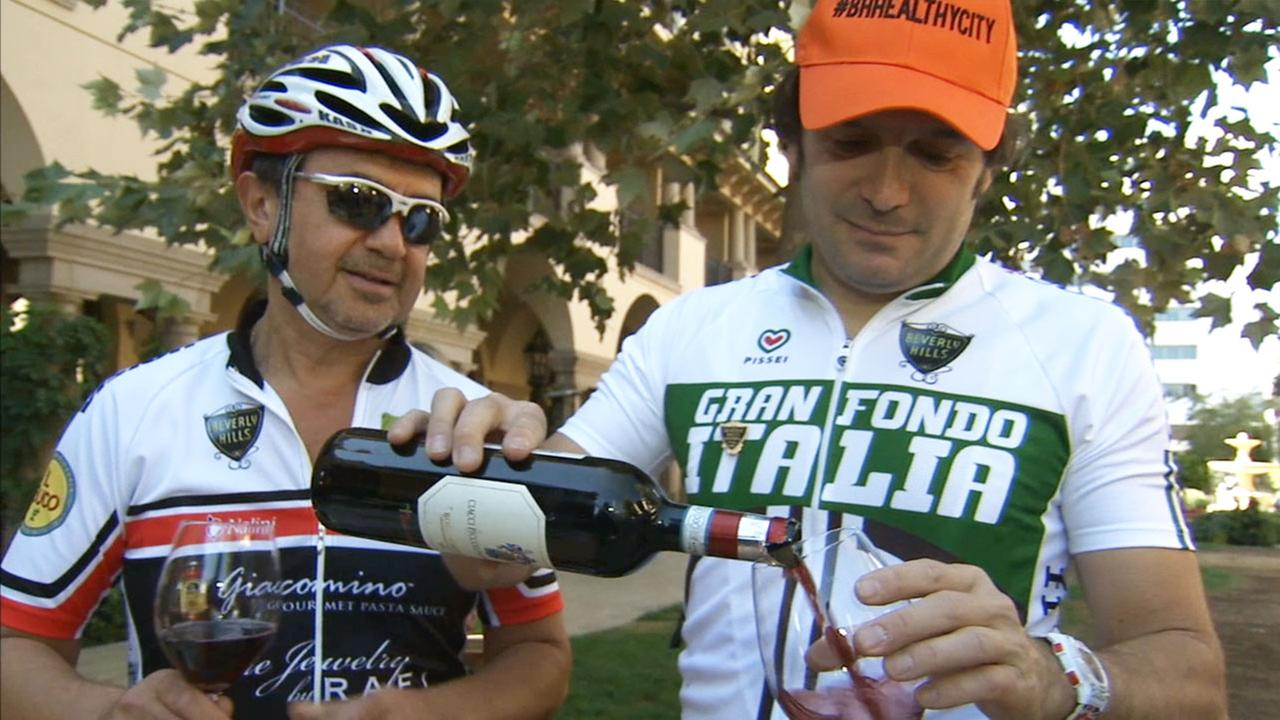 Gran Fondo Italia creator Matteo Gerevini shares a glass of wine with another cycling enthusiast.