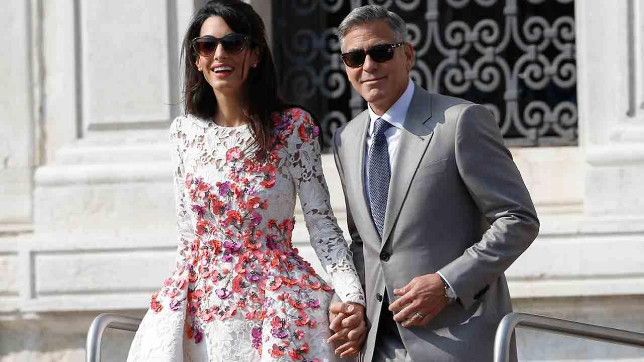 George Clooney is flanked by his wife Amal Alamuddin as they leave the Aman luxury Hotel in Venice, Italy, Sunday, Sept. 28, 2014.