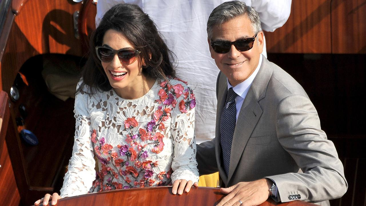 George Clooney and his wife Amal Alamuddin, cruise the Grand Canal after leaving the Aman luxury Hotel in Venice, Italy, Sunday, Sept. 28, 2014.
