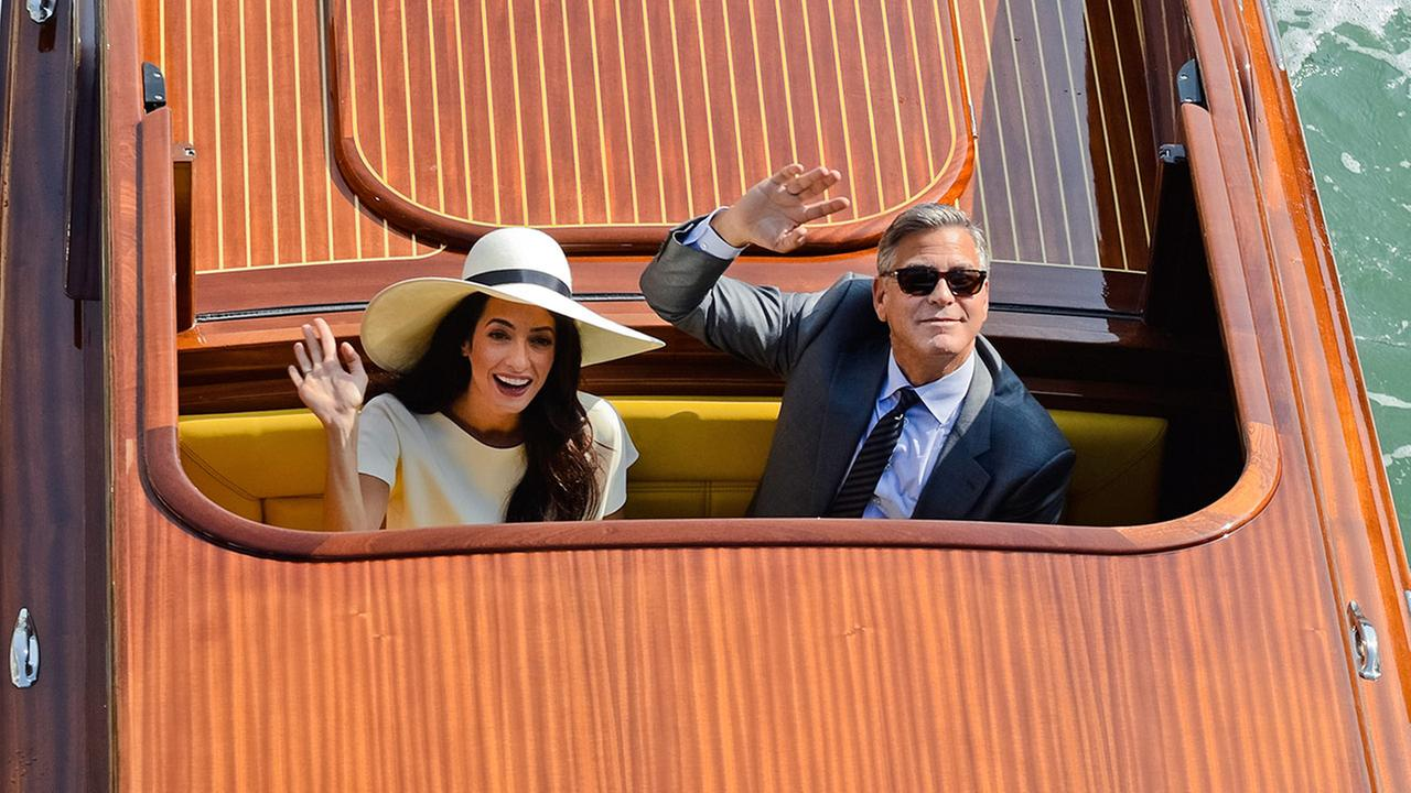 Actor George Clooney and his wife Amal Alamuddin wave from a boat as they leave after a civil weeding ceremony at the town hall in Venice, Italy, Monday, Sept. 29, 2014.AP Photo/Luigi Costantini