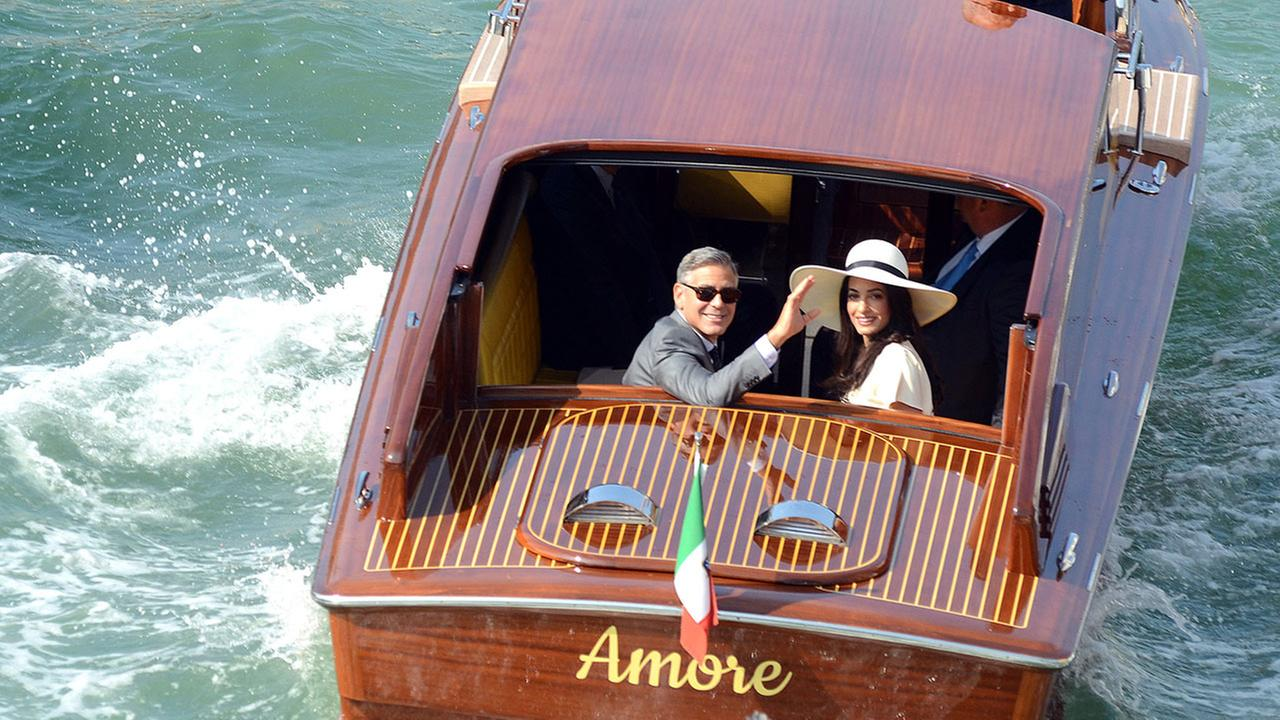 George Clooney, flanked by his wife Amal Alamuddin, waves from a water-taxi after leaving Venices city hall following their civil marriage ceremony on Monday, Sept. 29, 2014.AP Photo/Luigi Costantini