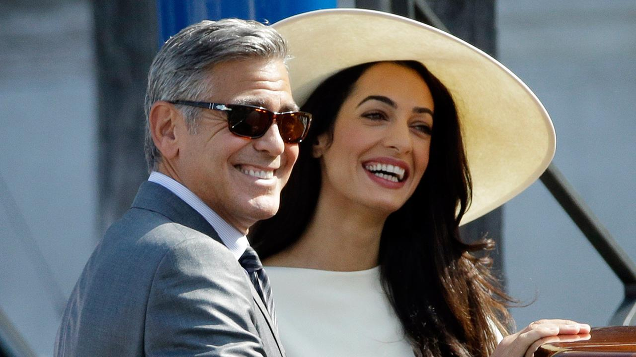 George Clooney and his wife Amal Alamuddin leave Venices city hall after their civil marriage ceremony on Monday, Sept. 29, 2014.