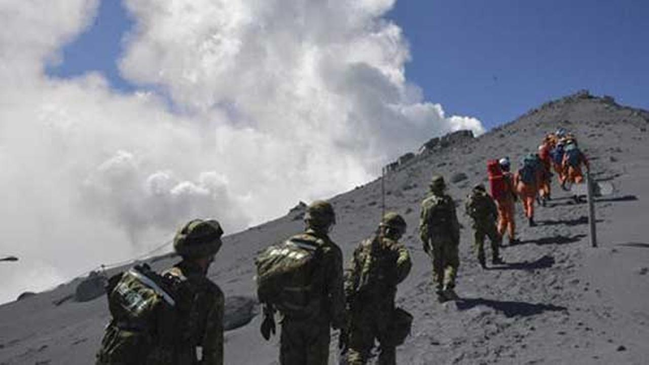 JGSDF personnel and fire fighters head for the summit of Mount Ontake to rescue people who were trapped, one day after the volcano became active.