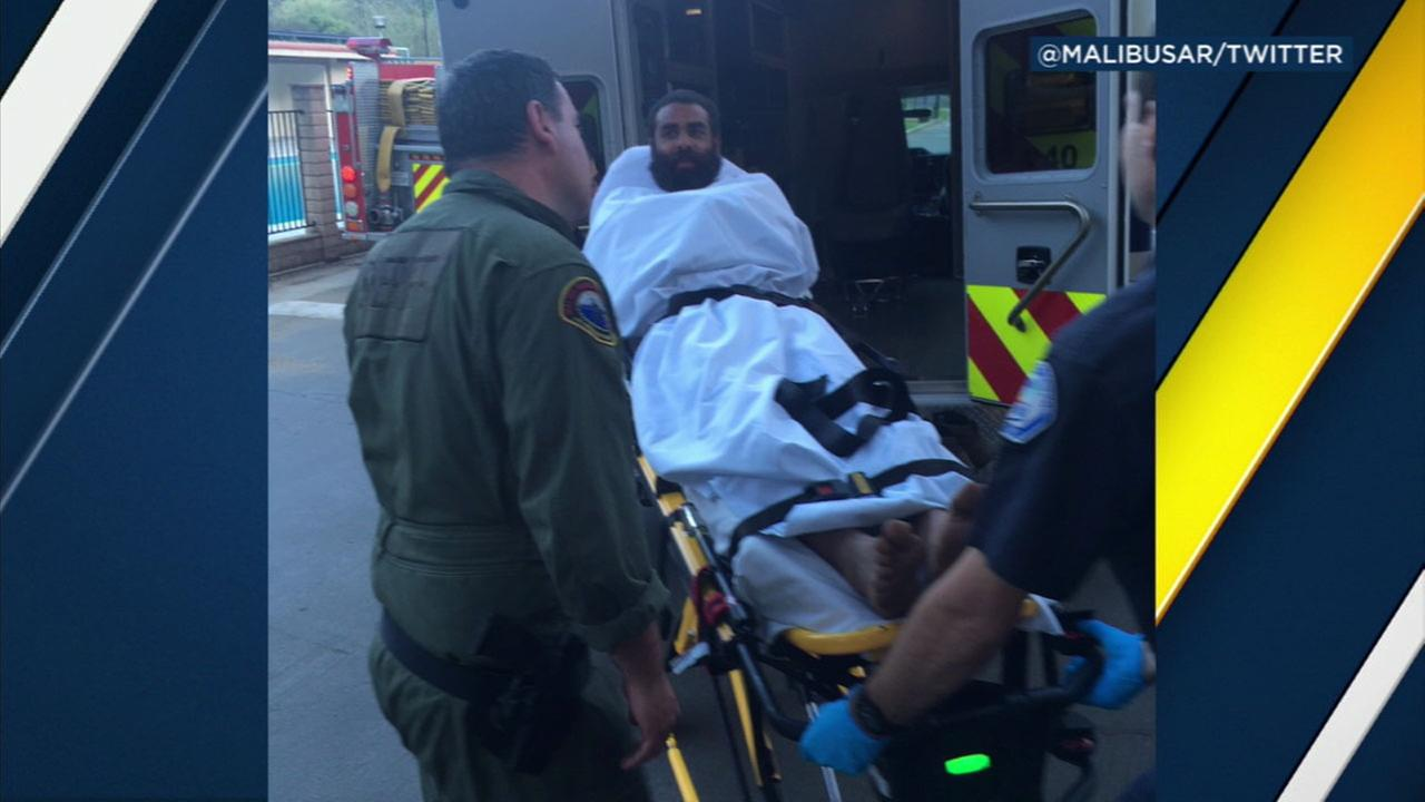 Marcelo Santos, 30, is shown being wheeled into an ambulance after being rescued in Malibu.