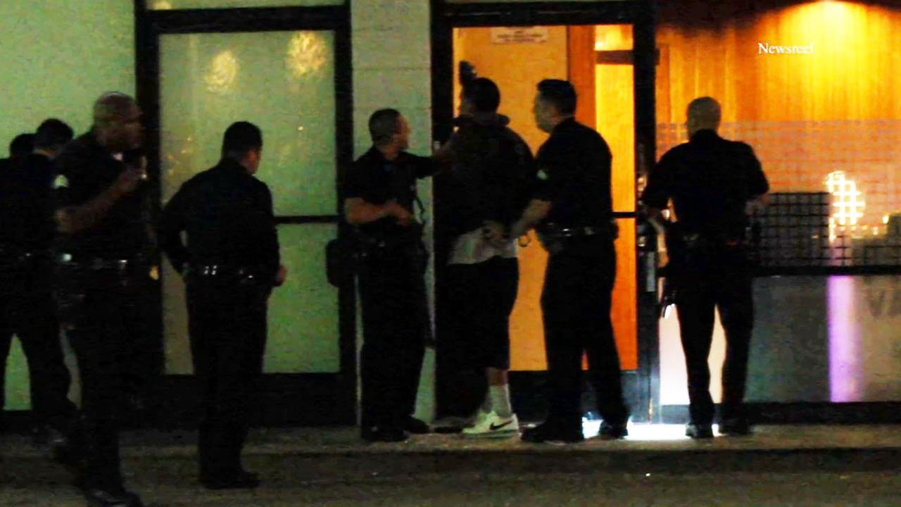 Law enforcement officers place handcuffs on a suspect in a burglary of a medical marijuana shop on the 11700 block of Ventura Boulevard in Studio City on Tuesday, Sept. 30, 2014.