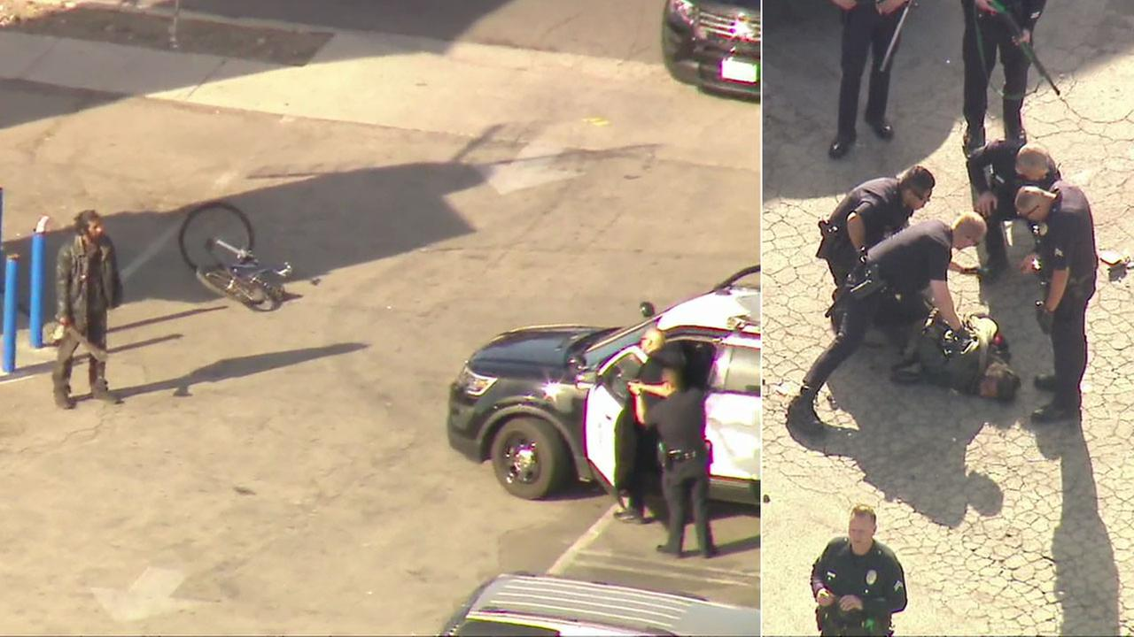 A man wielding a machete is shown as officers try to subdue him in a Pacoima parking lot. Another photo shows him being taken into custody.