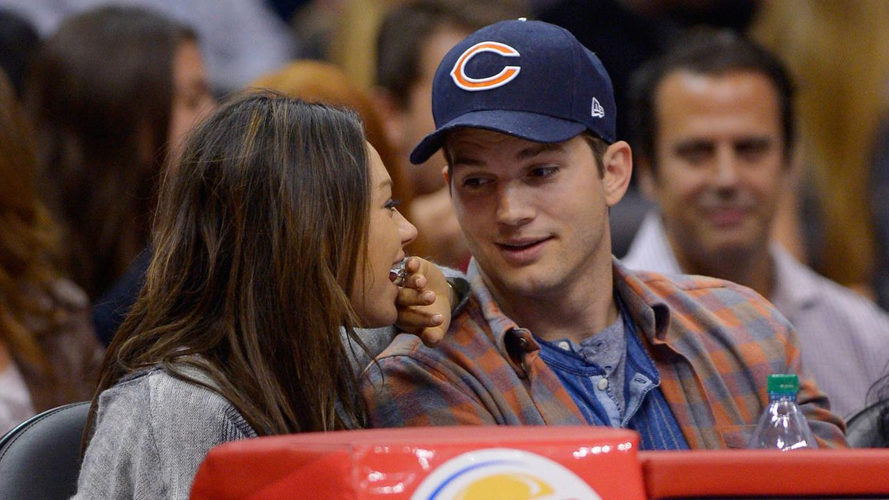 Actors Mila Kunis, left, and Ashton Kutcher watch the Los Angeles Clippers play the Detroit Pistons during the second half of an NBA basketball game Saturday, March 22, 2014, in Los Angeles.