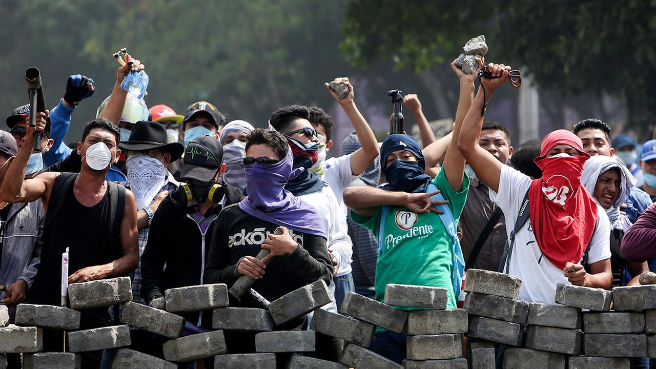 Protesters yell from behind the roadblock they erected as they face off with security forces in Managua, Nicaragua, Saturday, April 21, 2018.