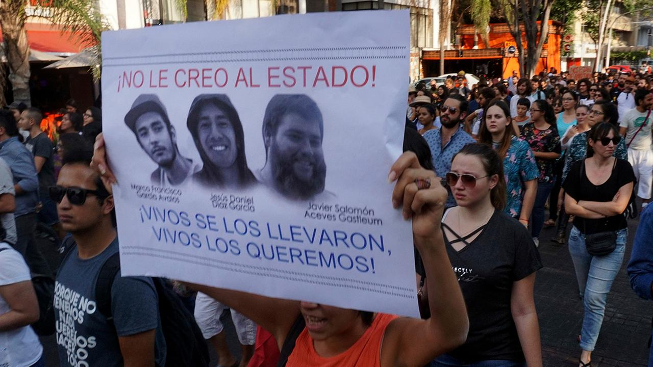 A student holds a sign with the portraits of three film students who have become emblematic of Mexicos missing, which reads in Spanish: I dont believe the government!