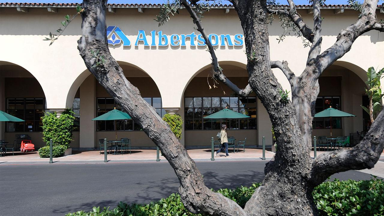 A customer walk near the entrance to a Albertsons grocery store in Tustin, Calif., Monday, Sept. 19, 2011.