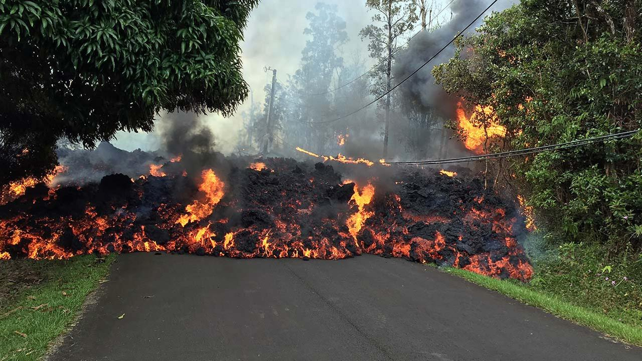In this Sunday, May 6, 2018 photo provided by the USGS, lava flow moves across Makamae Street in the Leilani Estates subdivision near Pahoa on the island of Hawaii.