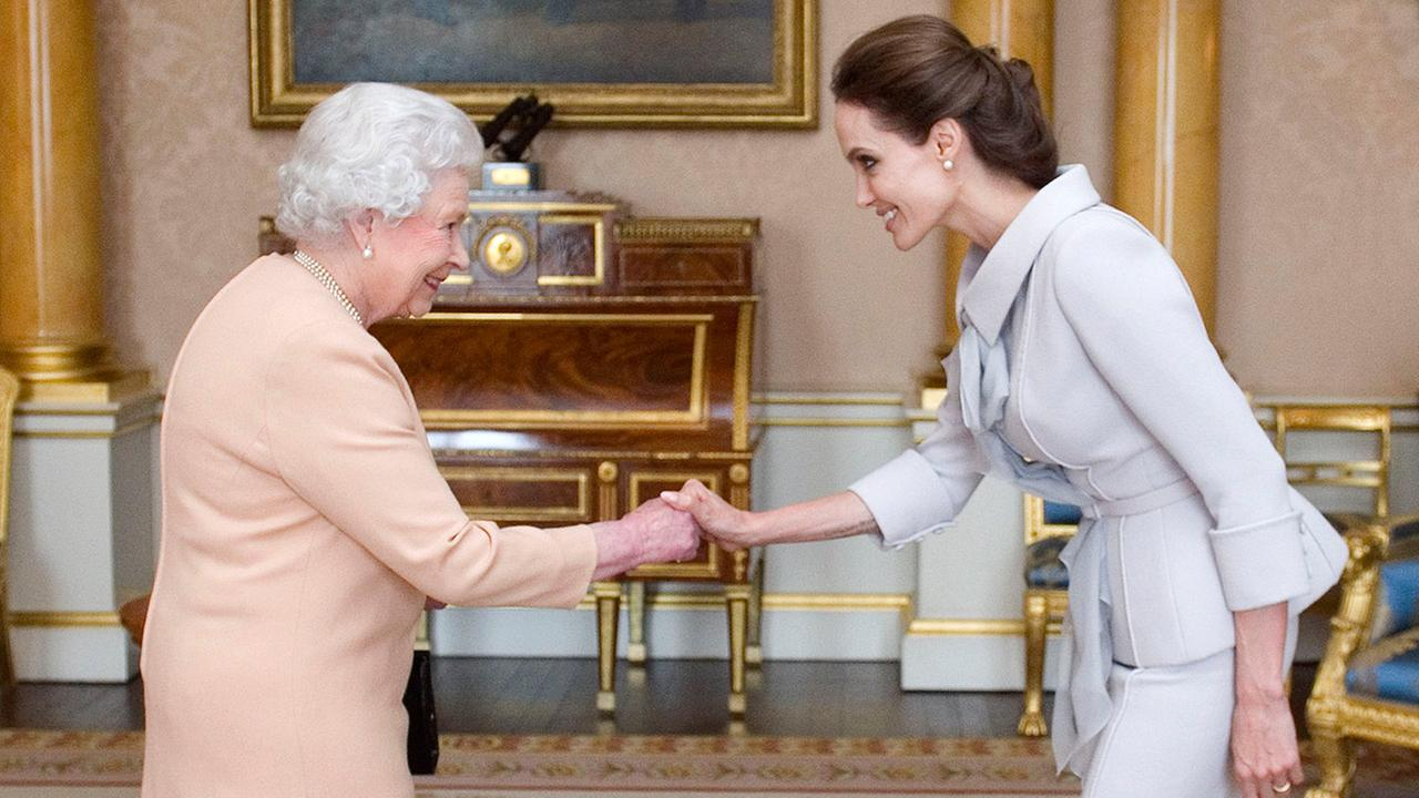 Actress Angelina Jolie, right, is presented with the Insignia of an Honorary Dame Grand Cross of the Most Distinguished Order of St Michael and St George by Britains Queen Elizabeth II at Buckingham Palace, London, Friday, Oct. 10, 2014.