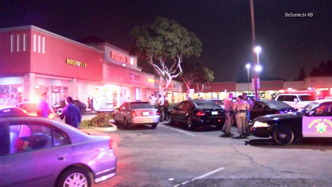Law enforcement officials are shown at the scene of an officer-involved shooting outside of a strip mall in Artesia on Saturday, Oct. 11, 2014.